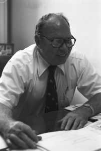 Arthur P. Leary sits at a desk