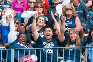 CWRU students and fans cheering in the stands at the homecoming football game
