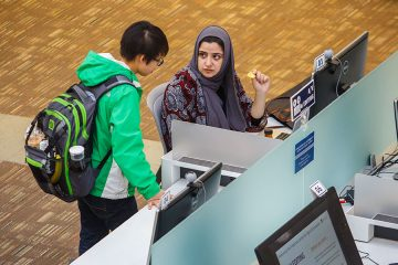 Overhead view of two students working at a computer in the library