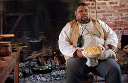 Michael Twitty sitting in front of brick fireplace holding pan of food