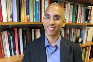 Photo of Deepak Sarma in front of a bookcase