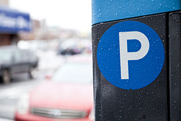 "Parking ticket machine with ""P"" parking symbol in focus and car off to the side"