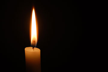 A single lit candle against a black background
