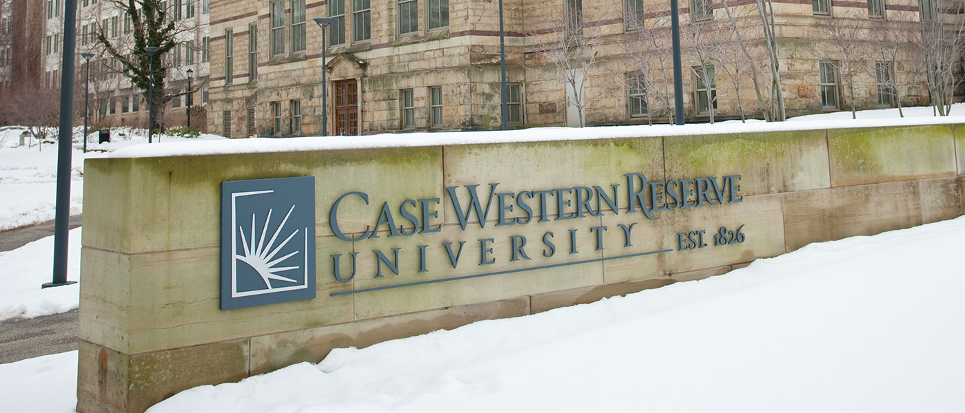 Case Western Reserve University sign in front of Adelbert Hall covered in snow