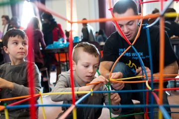 Student shows two children how to build structure at Engineering Challenges Carnival