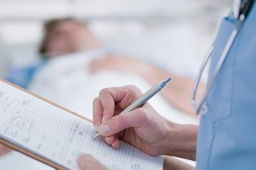 Photo of a nurse holding a patient's chart on a clipboard with a patient in bed in the background