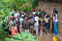 Rwandan villagers gather around engineering students