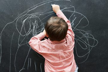 Child draws on a blackboard