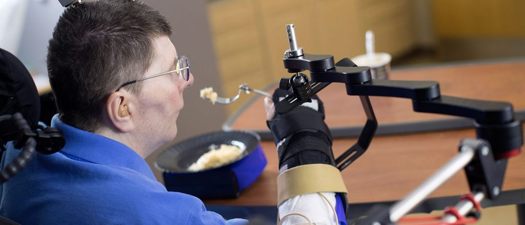 Photo of Bill Kochevar eating with help from temporarily implanted technologies