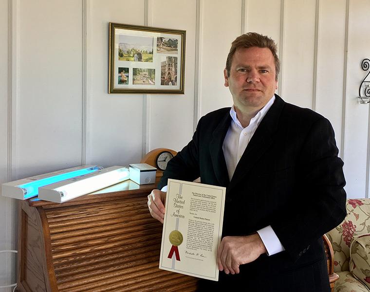 Inventor Doug DeWalt holds his patent on a UV light