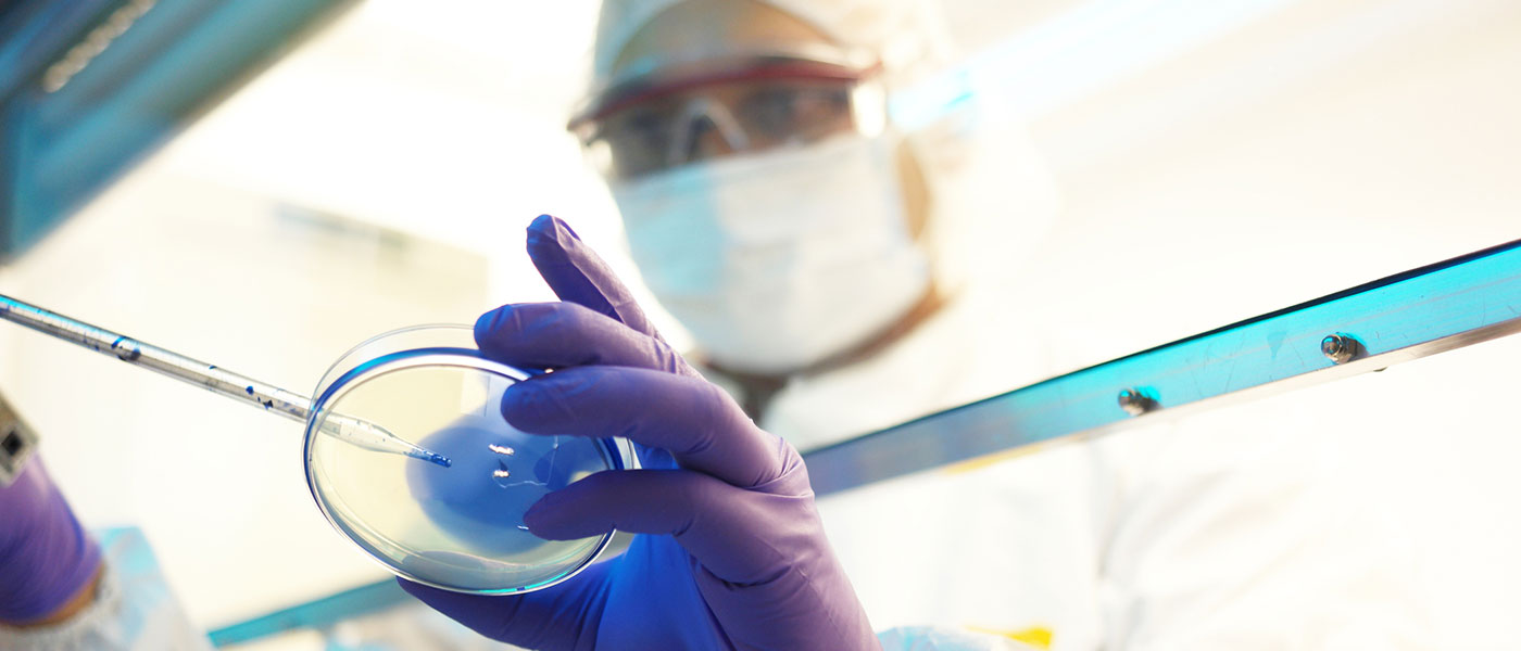 Photo of a biomedical researcher holding a pipette and petri dish in the lab