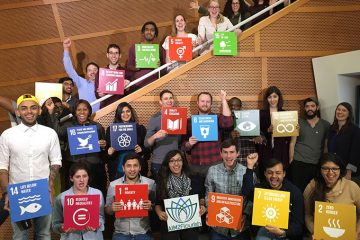 College students hold up placards illustrating each sustainable development goal