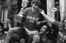Black and white photo of a team celebrating a Hudson Relays victory in front of Adelbert Hall