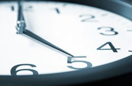 Close up on clock with hour hand pointing at 5