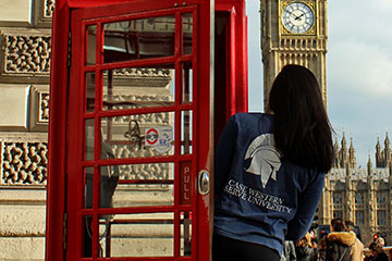 CWRU student looks at Big Ben from red phone booth in London