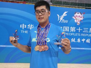 """Ye """"Duke"""" Li with multiple medals and holding a trophy in each hand"""
