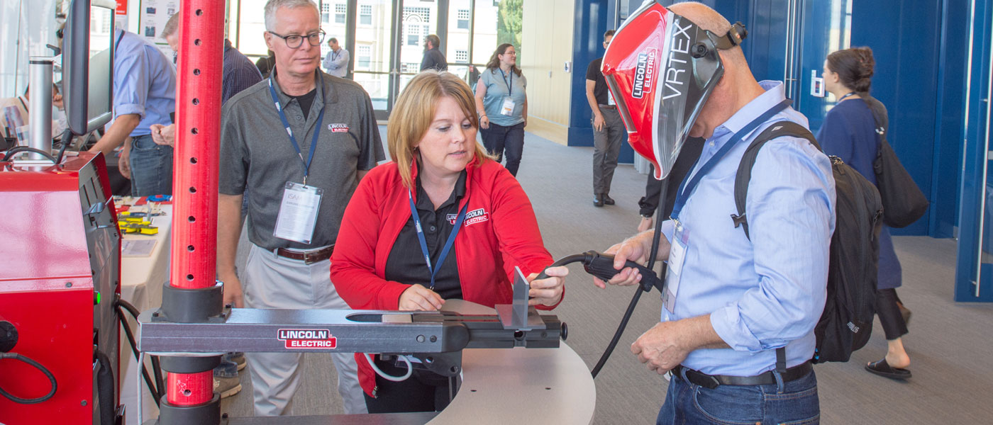 Photo of conference attendee using virtual reality welder.