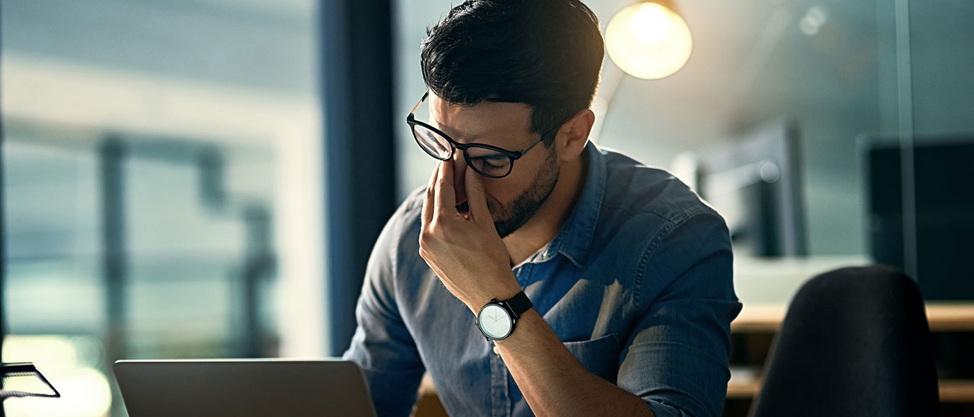 Photo of stressed businessman with hand on face at desk with laptop