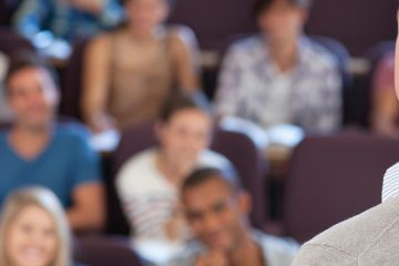 man standing in front of students in a lecture hall