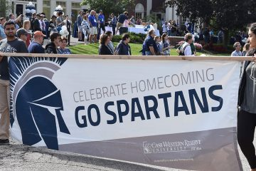 """Two individuals holding a banner that says """"Celebrate homecoming Go Spartans"""" during the homecoming parade"""