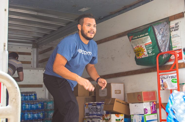 Photo of Edwin Colon standing in truck as he loads supplies into it