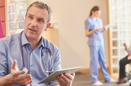 Photo of doctor talking to patient in waiting room