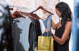Woman looks at an article of clothing from rack while shopping