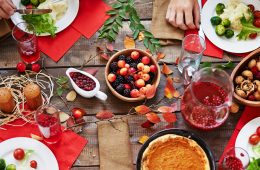 photo of a fall dinner table spread with pumpkin pie, cranberries and more