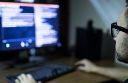 Photo of a man coding at computer