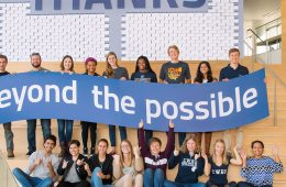 """Students hold a banner that says """"beyond the possible"""" with a sign behind them that says """"thanks"""""""