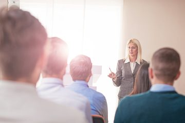 Woman giving lecture to group of people