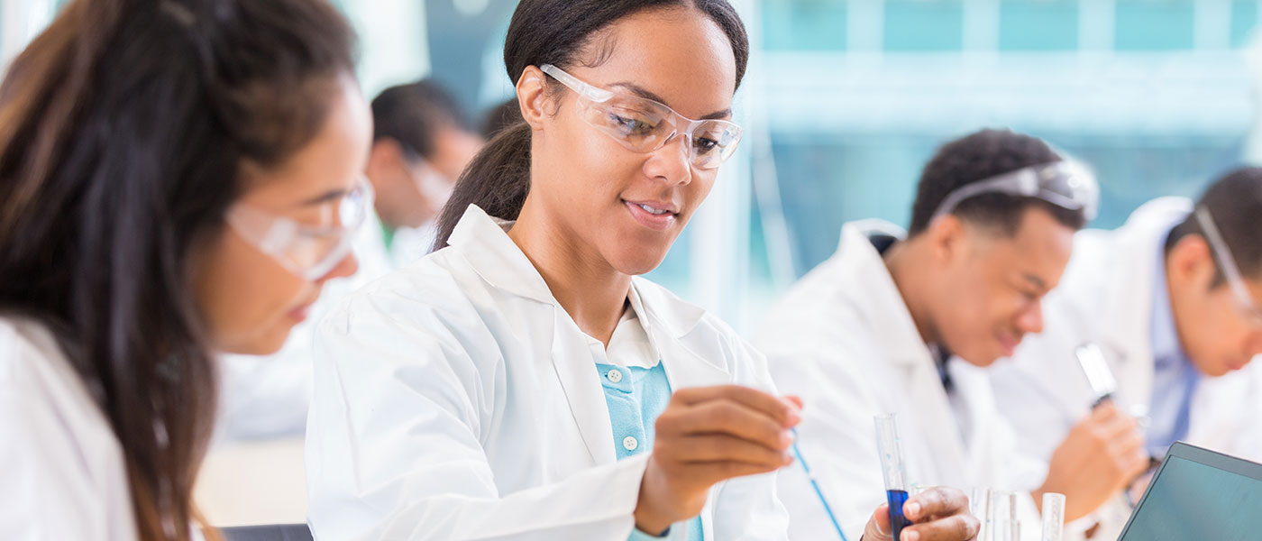 African-American female student drops liquid into a beaker with another student watching and two in the background