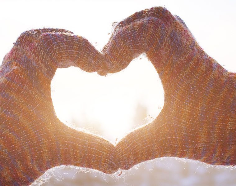 Gloved hands in the shape of a heart against wintry background