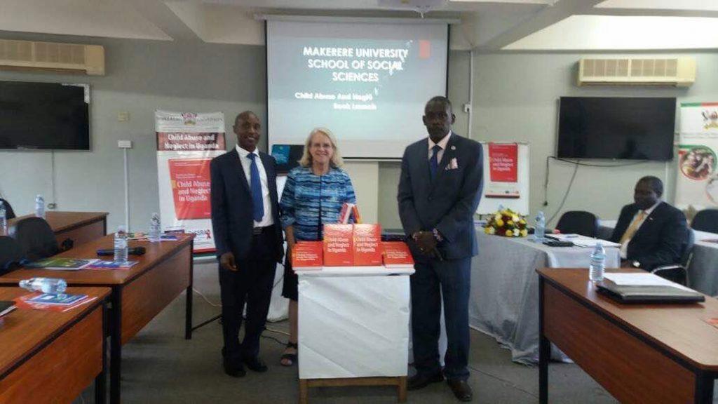 Photo of David Kaawa-Mafigiri, Jill Korbin and Eddy Walakira with table with books on it