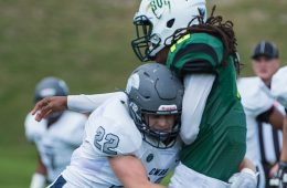 Photo of Zach Lyon tackling another player during a football game