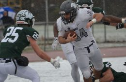 Aaron Aguilar runs with the football as other players try to tackle him