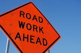 """Sign that says """"Road Work Ahead"""" against blue sky background"""