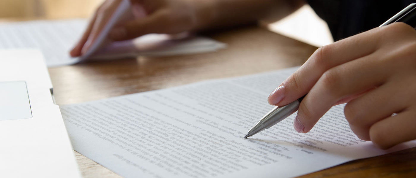 Hand holding a pen proofreading a paper