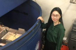Researcher Sophie Wang stands by a centrifuge