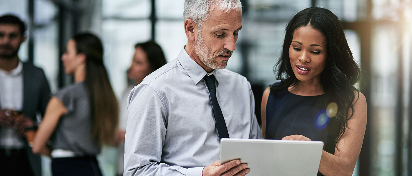 Two business professionals looking at a tablet