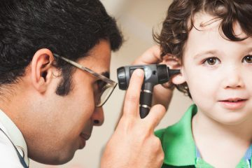 A doctor looking into a young boy's ear to check his hearing