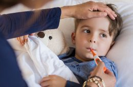 Sick child laying in bed with teddy bear while mom holds hand over his forehead and takes his temperature