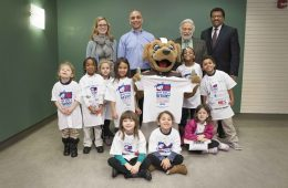 Children and administrators pose for photo during Give Kids a Smile Day