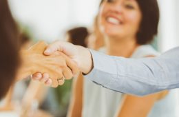 Photo of two people shaking hands at an interview or career fair with a woman smiling in the background