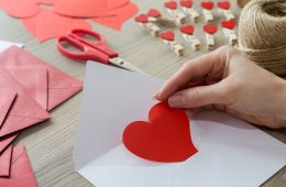 Photo of a woman's hand placing a heart-shaped paper in envelope