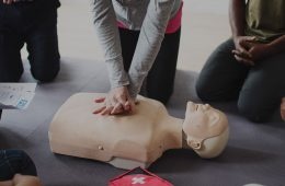 Person demonstrates CPR technique surrounded by people