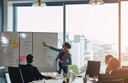 People in a business meeting with one person pointing at a whiteboard