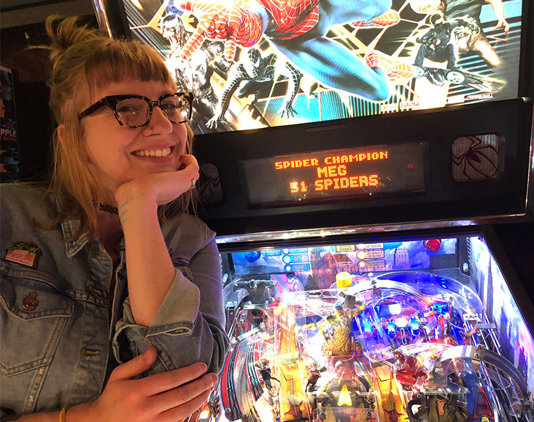 Photo of Megan Brown with a pinball machine