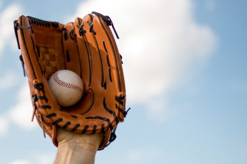 Photo of a baseball mitt with a ball in it as someone makes a catch