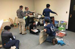 Students on Alternative Breaks program work together going through artwork